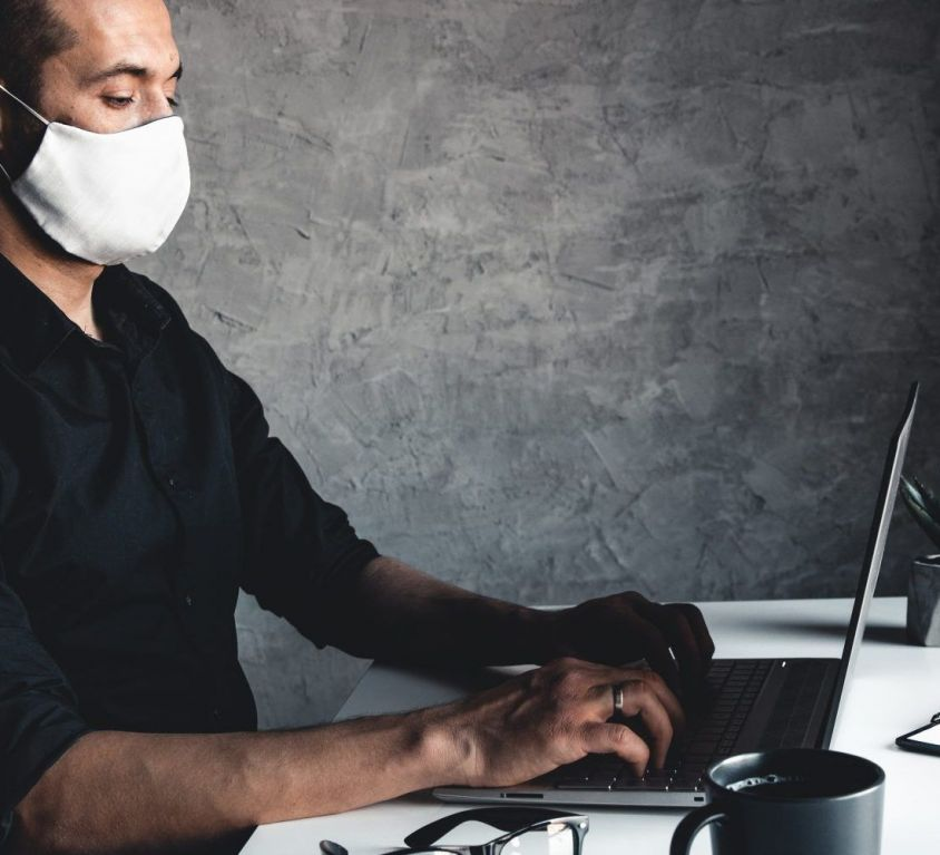 a-masked-man-works-at-a-computer-pandemic-coronavi-P7AH6B2-2048x1000